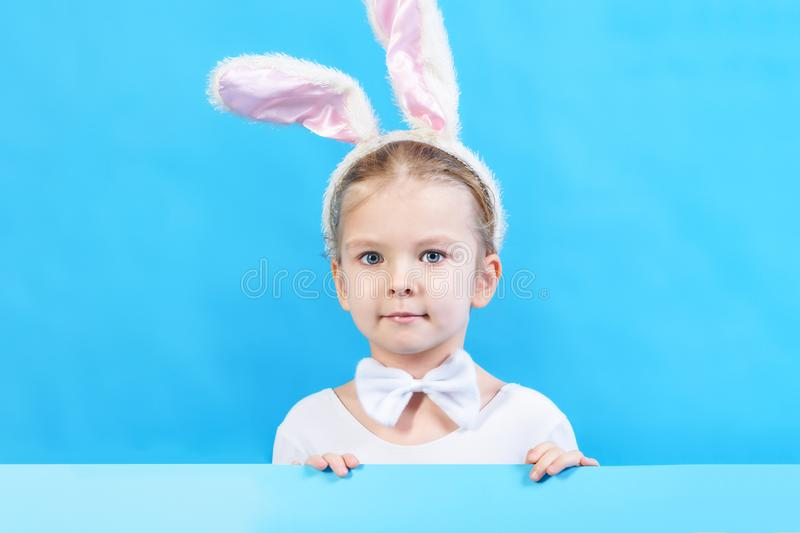 Little girl in a white rabbit costume holding a sheet of blue cardboard. Beautiful child, symbol of Easter holiday. Copy. Space. Advertising layout with place stock photos
