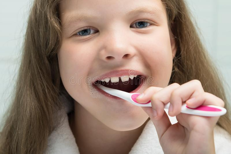 Little girl in a white robe smiling brushes her teeth, close-up stock photos