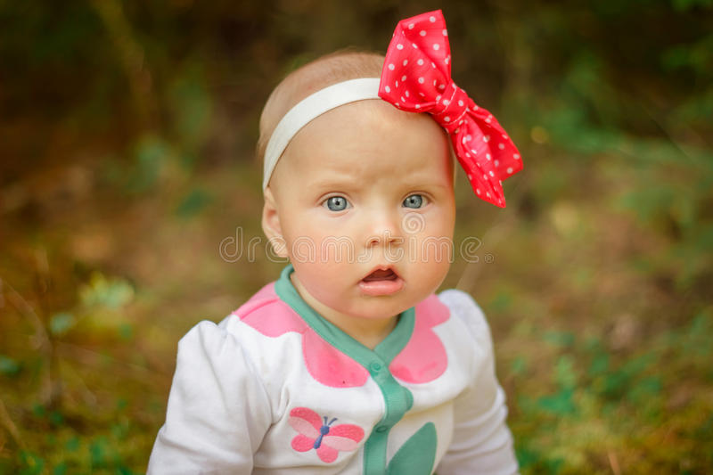 Little girl in a white suit with a red bow stock photos