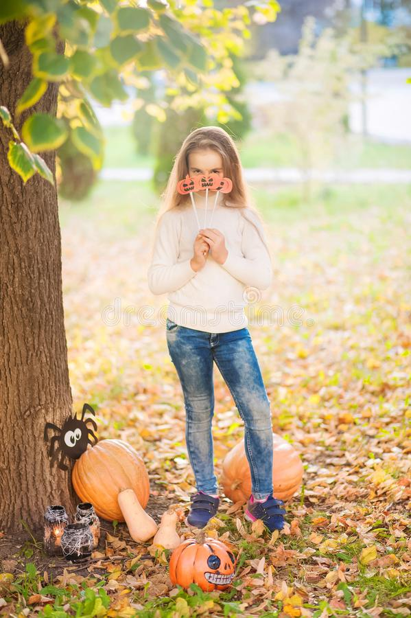 Little girl in a white sweater and jeans on a background of green textural natural background. The girl is near the pumpkins and c stock image