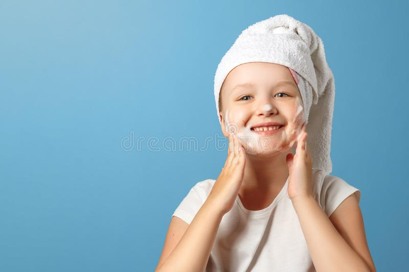Little girl with a white towel on her head washes on a blue background. The child laughs and uses foam on the face. The concept of stock images