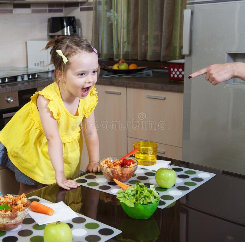 The little girl who is protesting against food. Cooked by his mother royalty free stock image