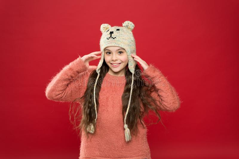 Little girl winter fashion accessory. Small child long hair wear hat red background. Cute model enjoy winter style royalty free stock image