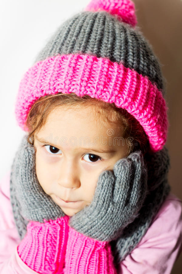 Little girl in winter hat with gloves and scarf. stock images