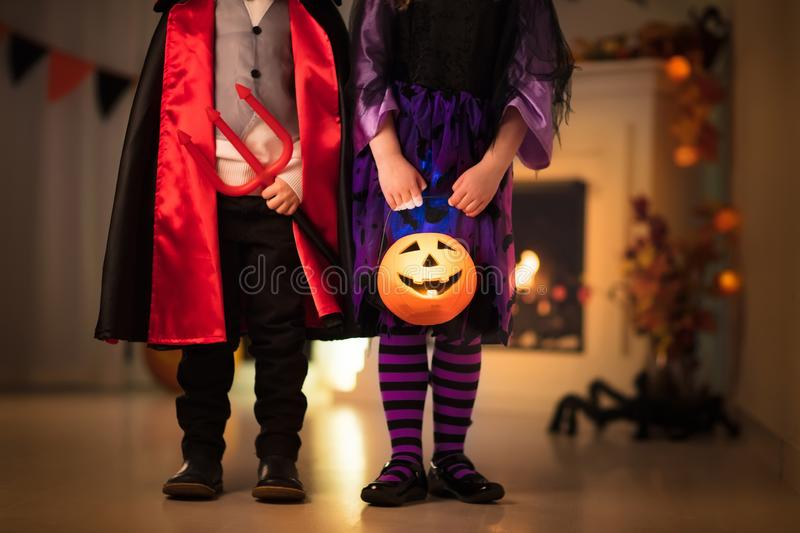 Kids in witch costume on Halloween trick or treat. Little girl in witch costume and boy dressed up as vampire on Halloween trick or treat. Children trick or stock images
