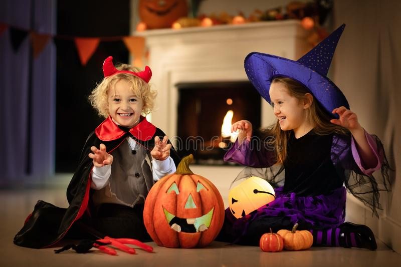 Kids in witch costume on Halloween trick or treat. Little girl in witch costume and boy dressed up as vampire on Halloween trick or treat. Children trick or royalty free stock photos