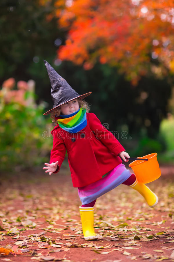 Little girl in witch costume at Halloween stock images