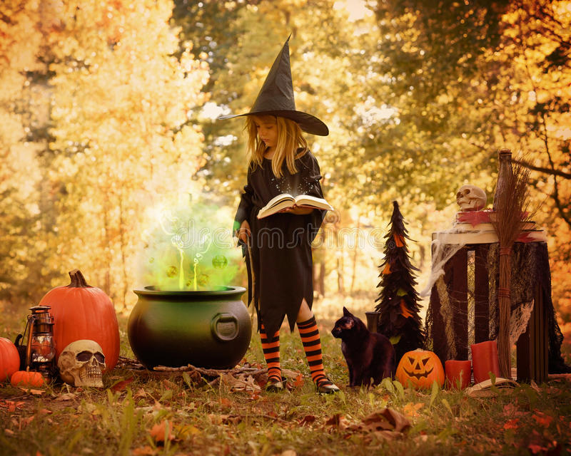 Little Girl in Witch Costume Outside with Magic Book stock photos