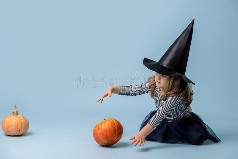 Little girl in witch hat and black clothing with playing with pumpkin over blue stock photo