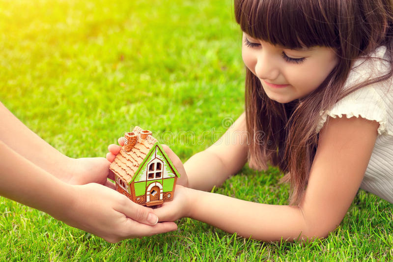 little girl and a woman hands holding small house on a background of green grass royalty free stock image