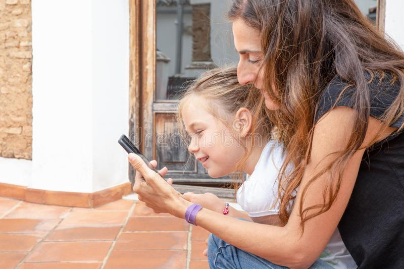 Little girl and woman watching mobile and smiling stock image