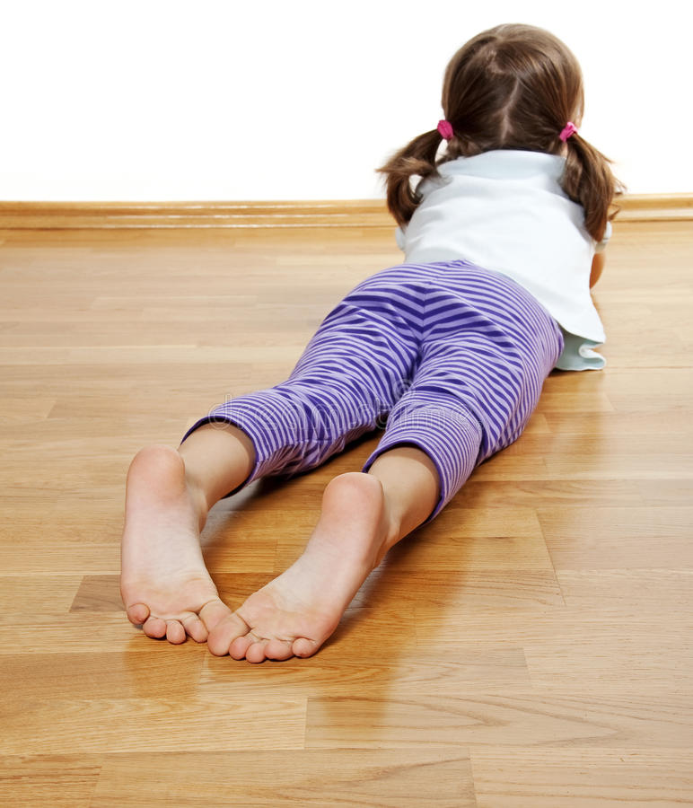A little girl on a wooden floor royalty free stock photography