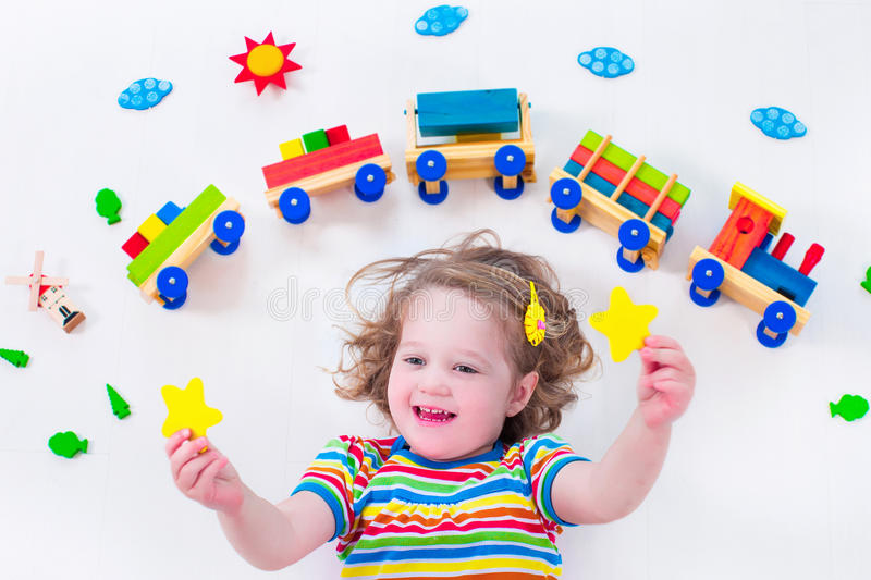 Little girl with wooden train. Child playing with wooden train. Toy railroad for kids. Toddler kid at day care. Educational toys for preschool and kindergarten stock photography