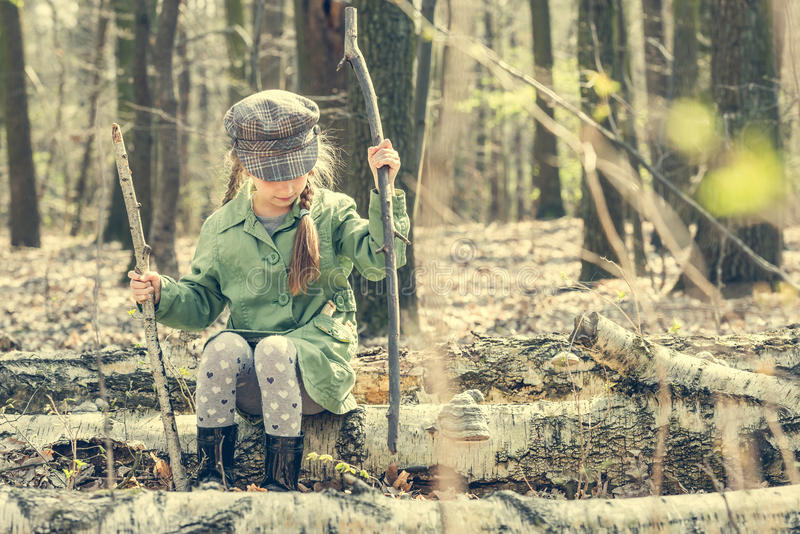Little girl in the woods sitting on a stump stock photo