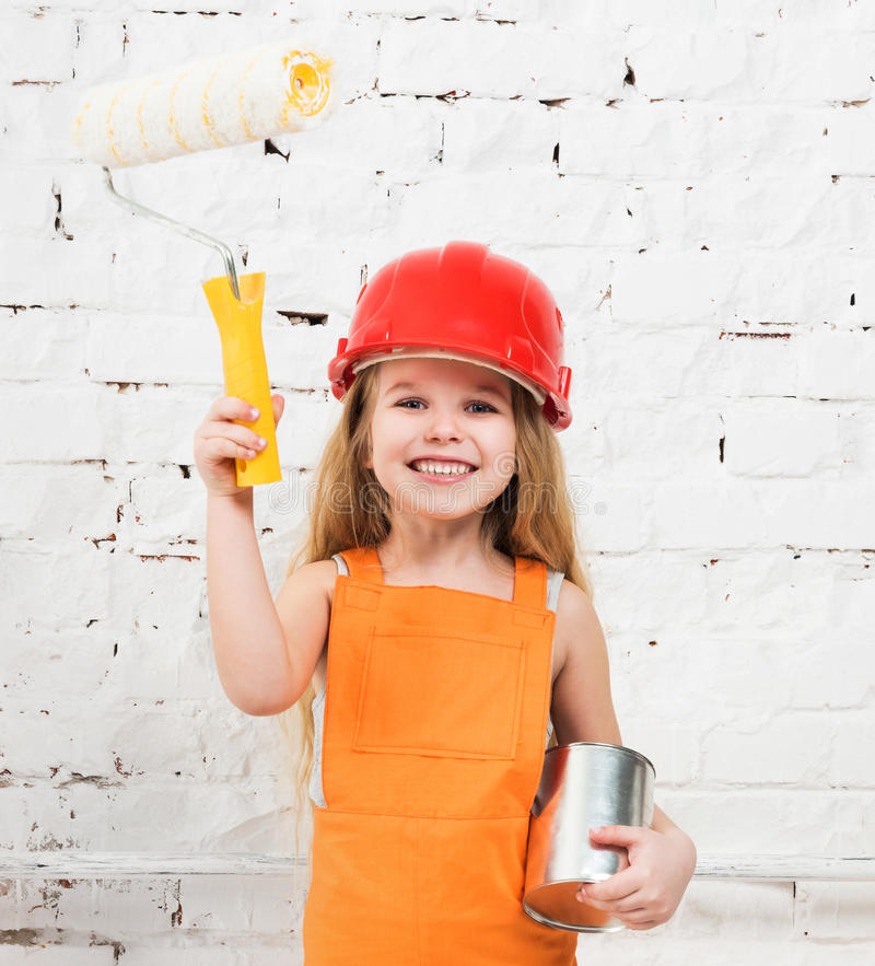 Little girl-worker with paint and roller in hands stock image