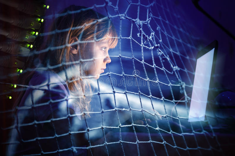 Little girl working on laptop at night in a fishing net royalty free stock photo