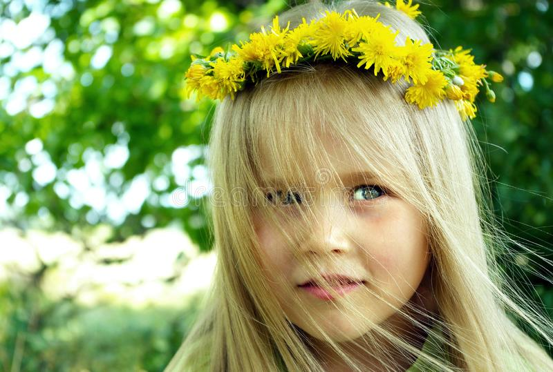 Little girl in a wreath. child among the flowers. royalty free stock photography