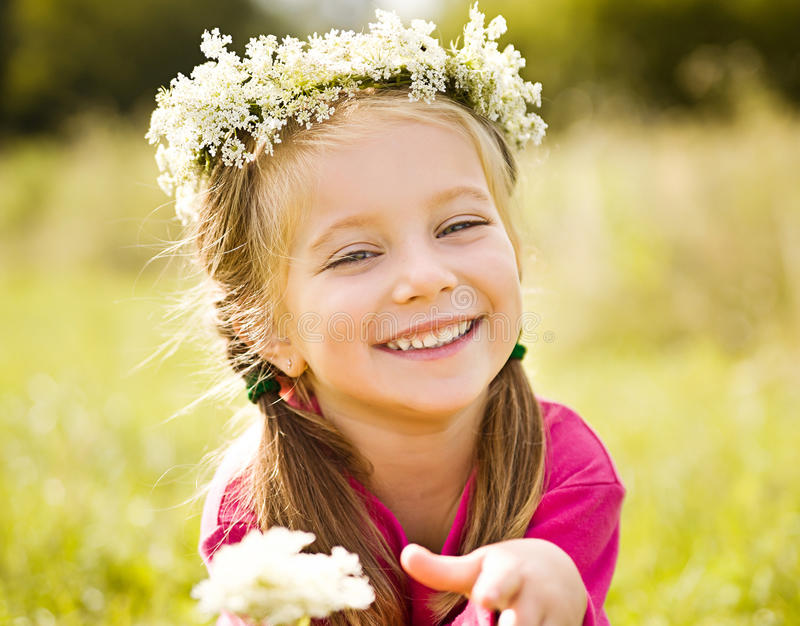 Little girl in wreath of flowers stock photos