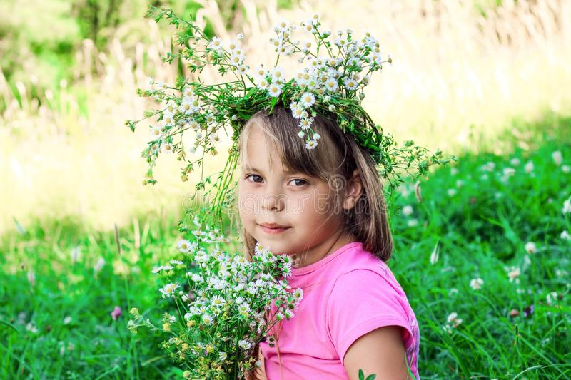 Little girl with a wreath of flowers on her head. stock images