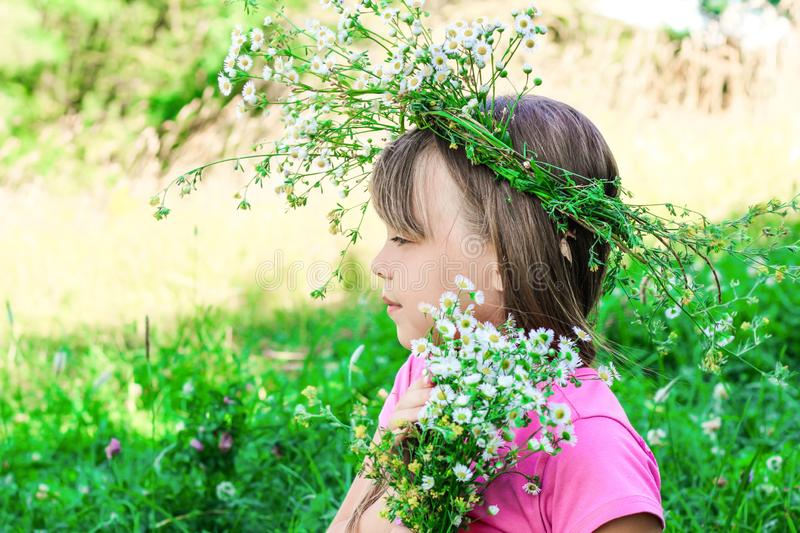 Little girl with a wreath of flowers on her head royalty free stock photos