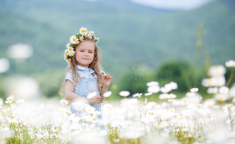 Little girl in a wreath of white daisies royalty free stock photos