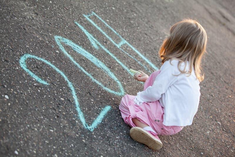 Little girl writing 2014 on asphalt royalty free stock photo