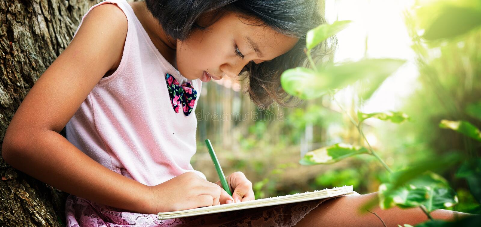 Little girl writing a book under atree. Little girl sitting under a tree and writing a book. her it is very concentrated royalty free stock photography