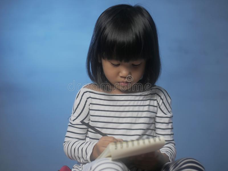 Little Girl Writing on Notepad stock photography