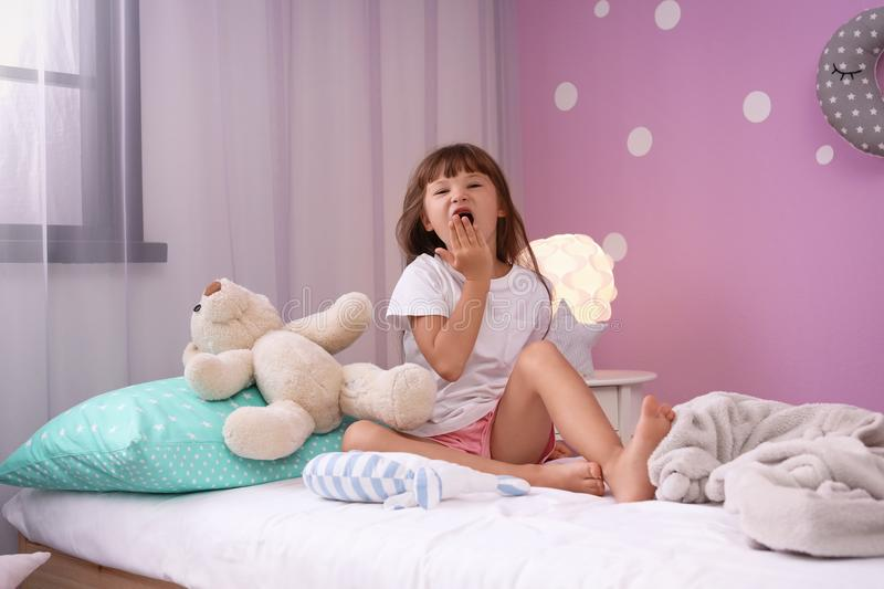 Little girl yawning on bed at home stock images