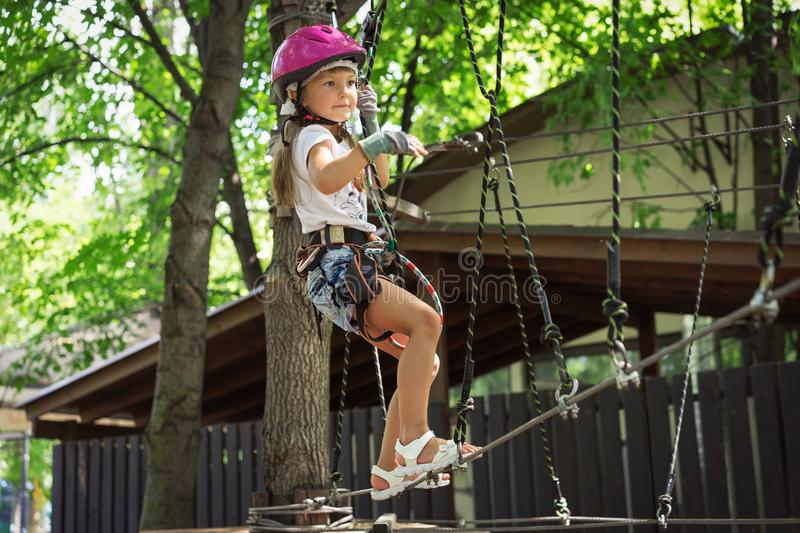 Little girl 5 years old climbing on an obstacle in a rope park in summer stock images