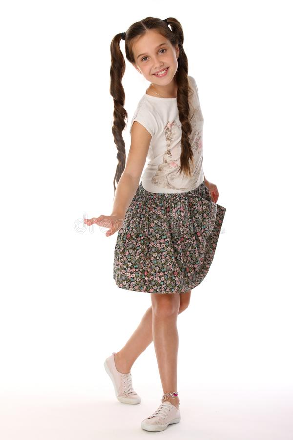 Portrait of a pretty young teenage girl 12 years old in a skirt with bare legs royalty free stock images