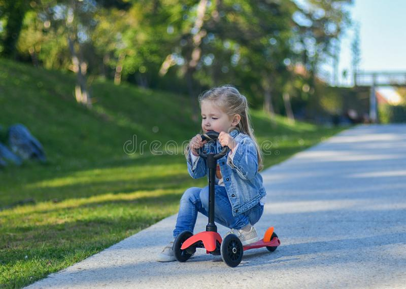 Little girl is riding a scooter royalty free stock photos