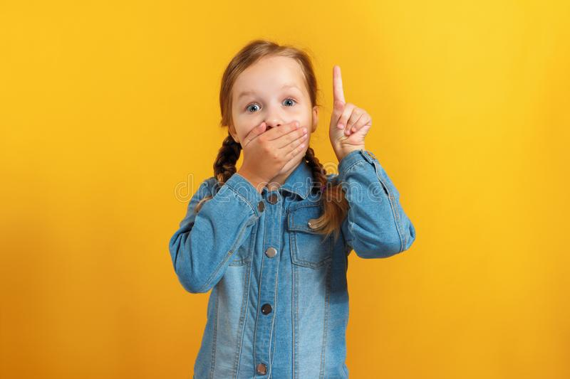 Little girl on a yellow background. The child is amazed by closing his mouth with his hand and pointing with an index finger to an stock photo