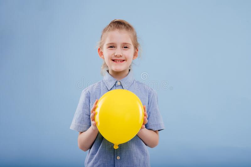 Little girl with yellow balloon with smile. royalty free stock photography