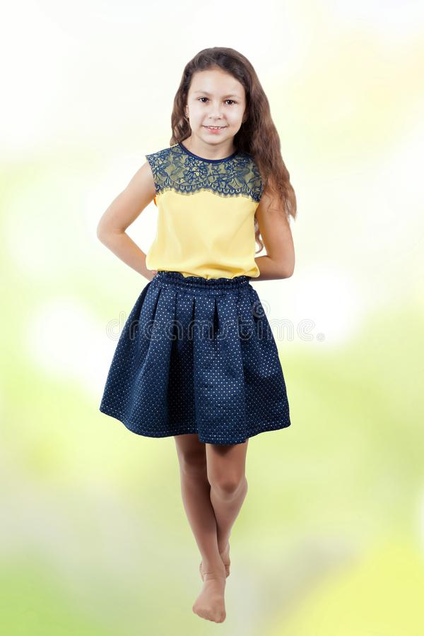 Little girl in a yellow blouse on a bokeh background royalty free stock photo
