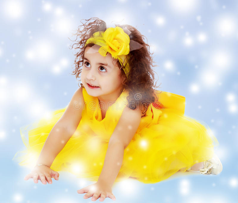 Little girl in yellow dress sitting on the floor royalty free stock photo