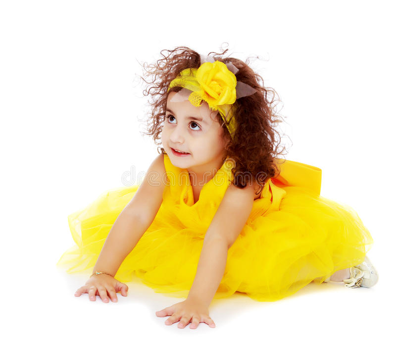 Little girl in yellow dress sitting on the floor stock images