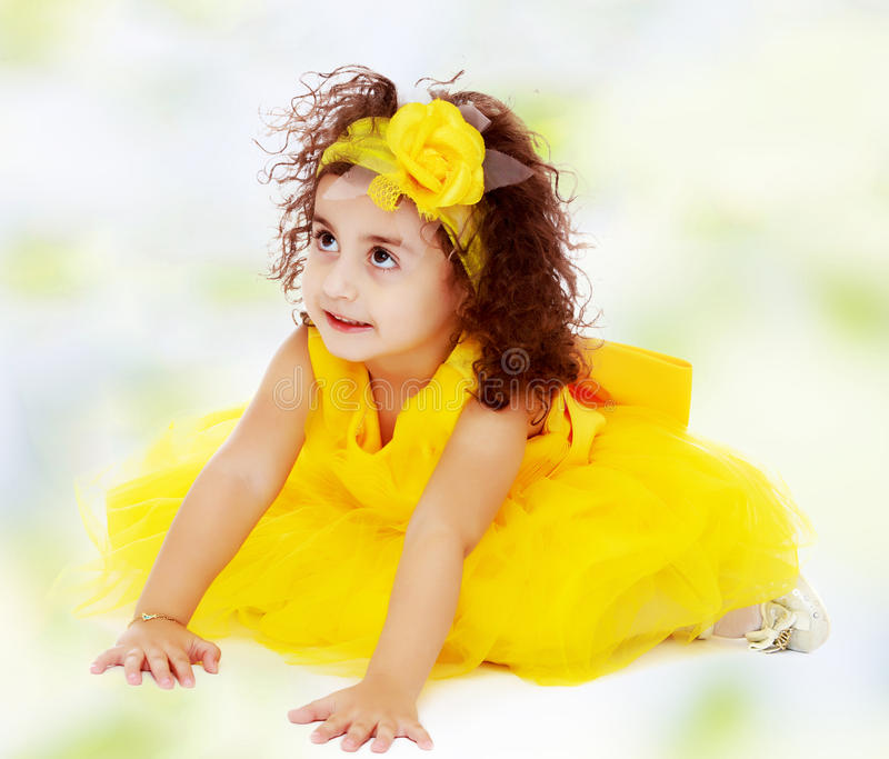 Little girl in yellow dress sitting on the floor royalty free stock photography