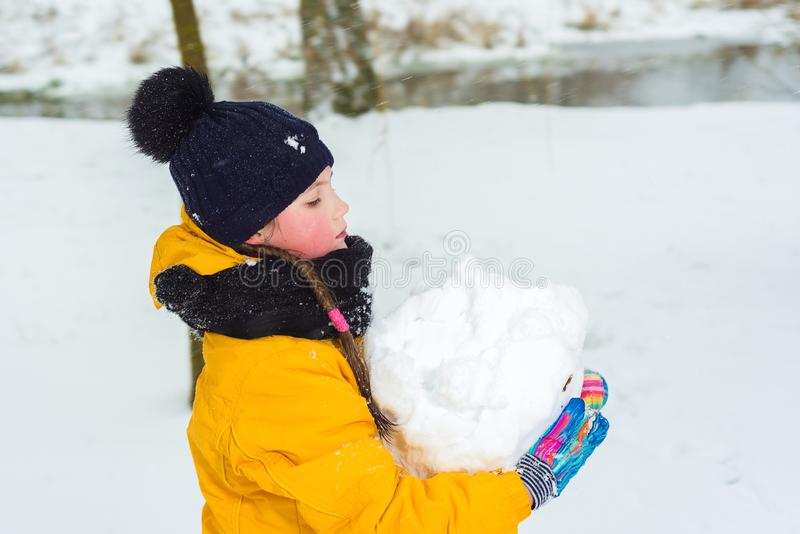 Little girl in a yellow jacket and winter hat is carrying a large snowball. girl makes a snowman royalty free stock image