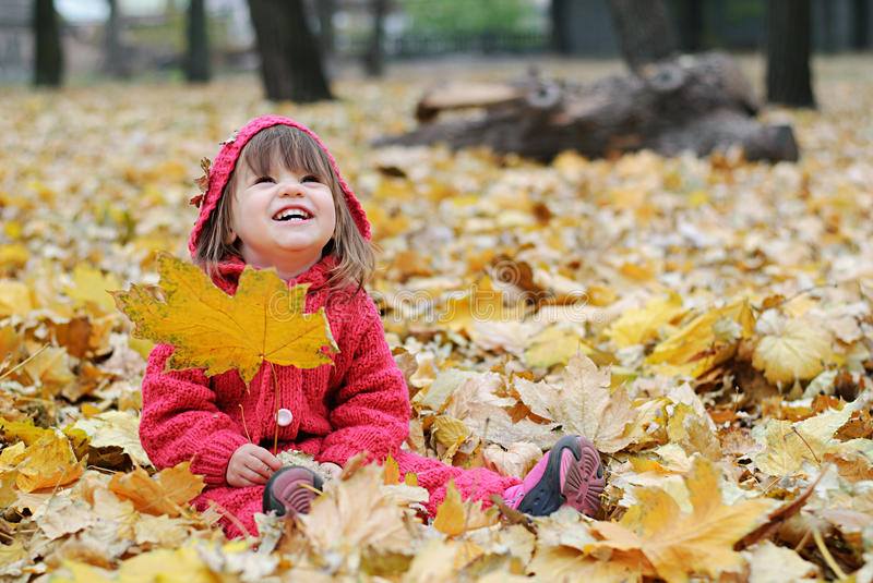 A little girl in yellow leaves stock photography