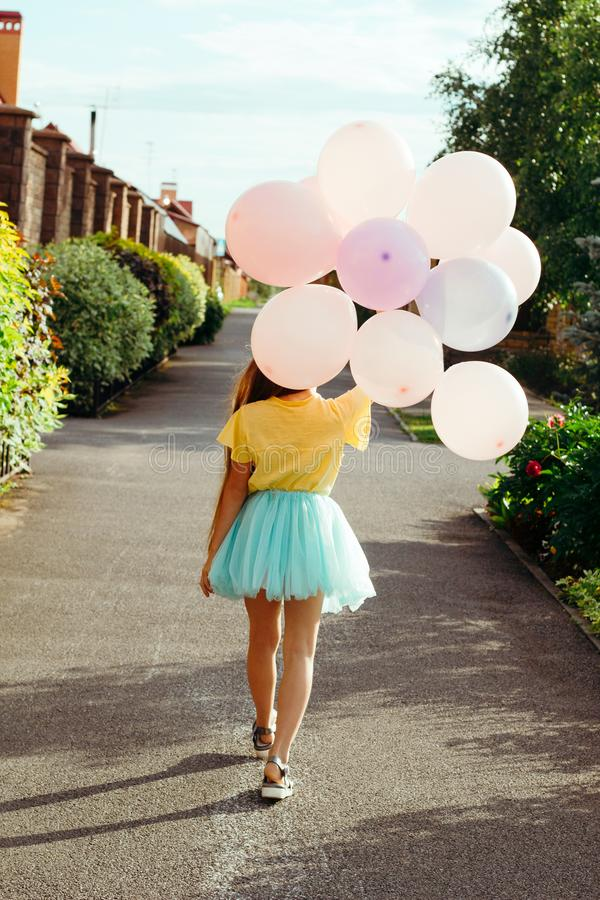 Girl in a yellow t-shirt and a blue tutu skirt holds a bunch of balloons and walks down the street with her back to the. Little girl in a yellow t-shirt and a royalty free stock photos