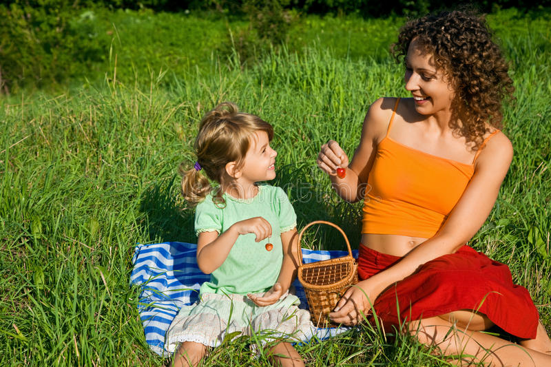 Little Girl And Young Women In Hand Sweet Cherries Stock Image