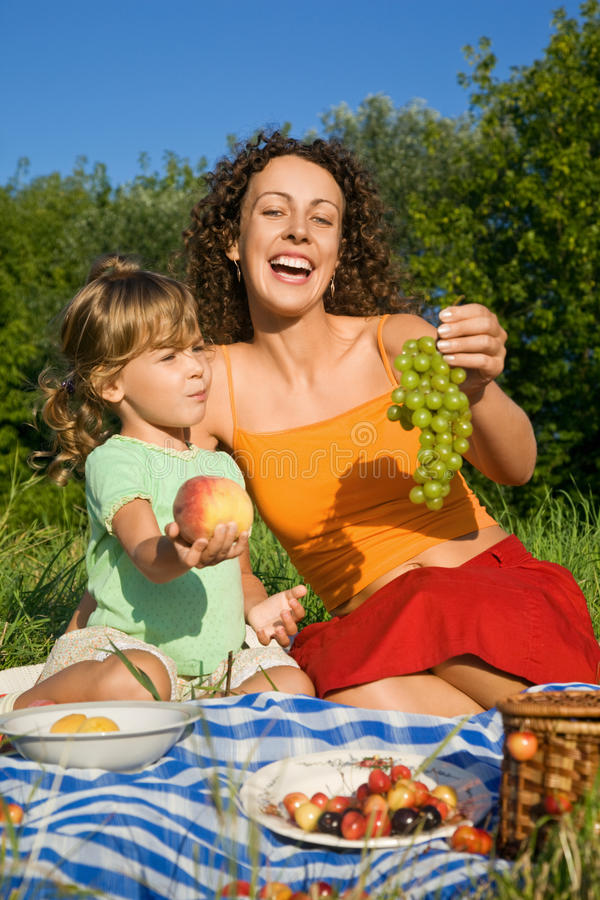 Little Girl and Young Women keeps in hand fruits royalty free stock photos