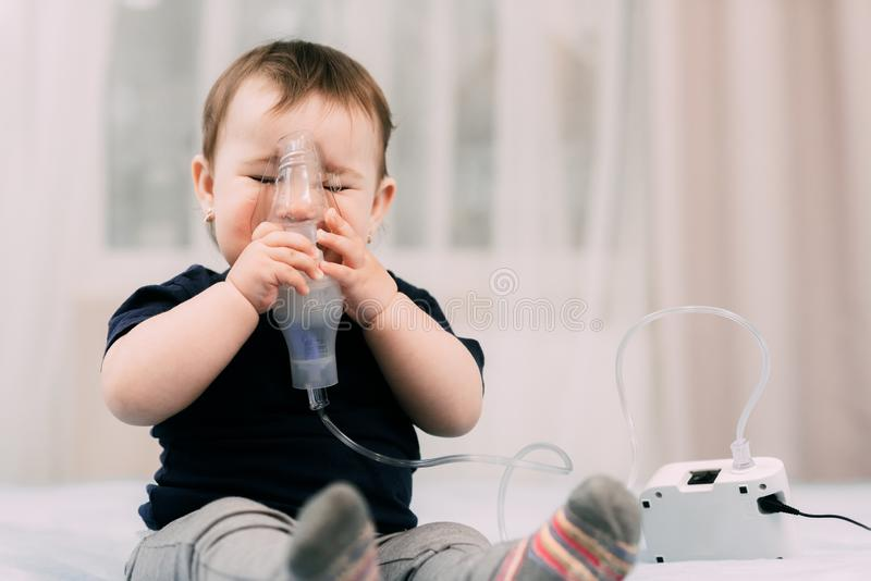 A little girl yourself holding the mask of the nebulizer, making inhalation royalty free stock photography