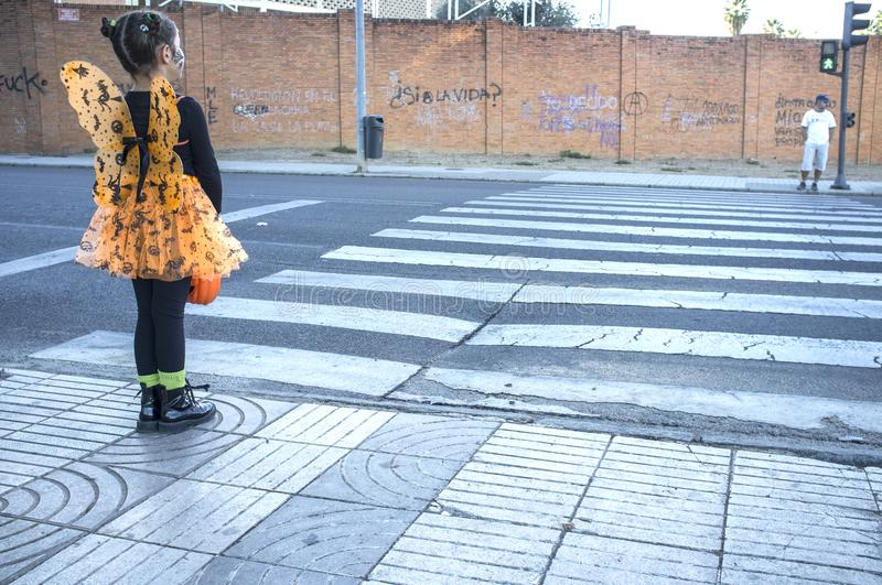 Little girl at zebra crossing in halloween costumes towards children party site stock photography