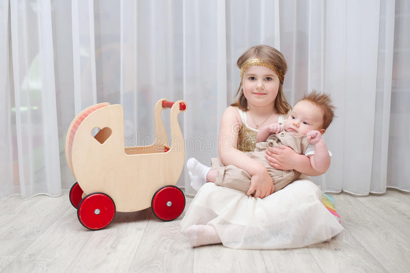 Little girld holds her younger brother. At home stock photos