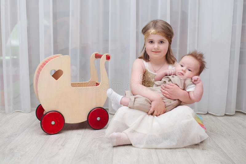Little girld holds her younger brother. At home stock image