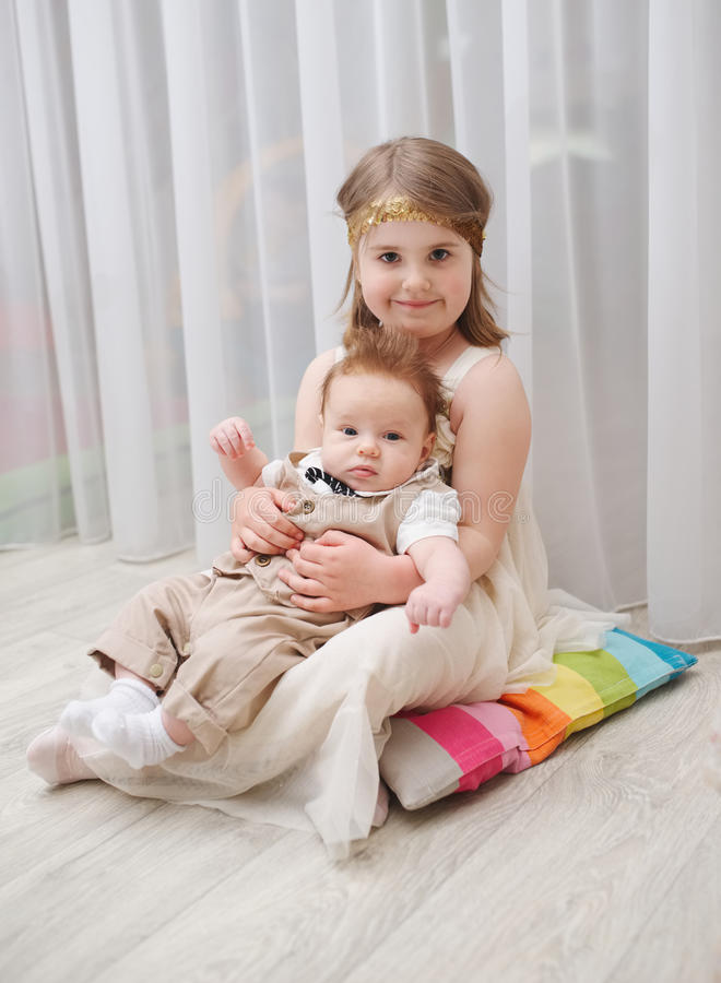 Little girld holds her younger brother. At home stock images