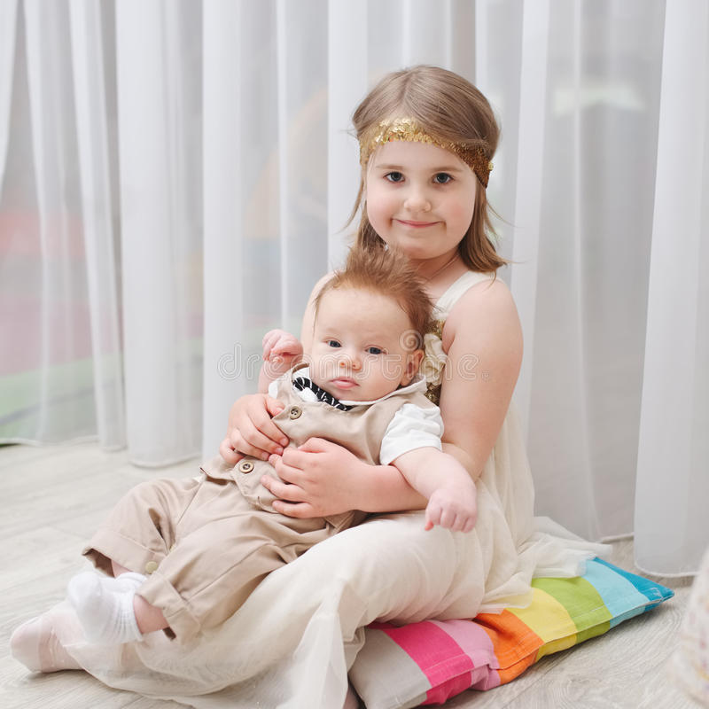 Little girld holds her younger brother. At home stock photography