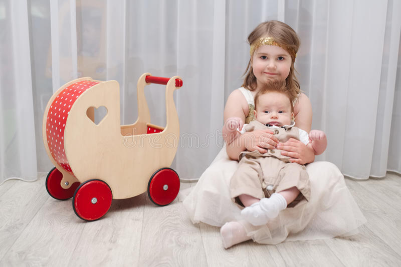 Little girld holds her younger brother. At home royalty free stock photo
